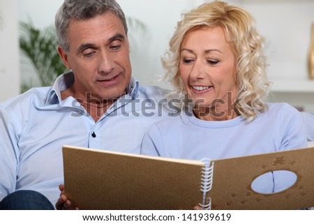 Couple looking at a photo album - stock photo
