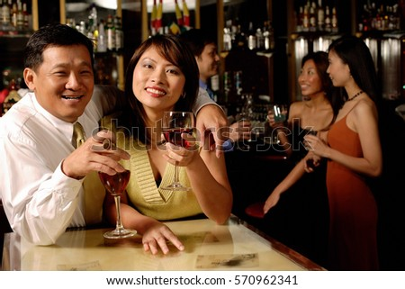 Couple looking at camera, holding wine glasses