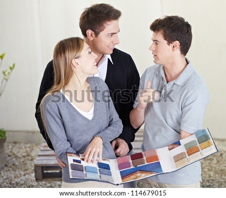 Couple looking at different carpet samples at floorlayer - stock photo