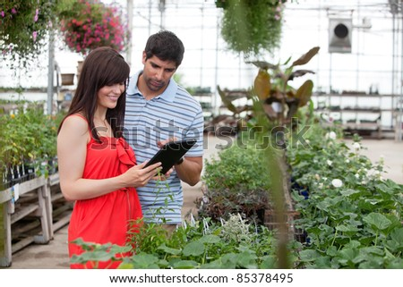 Couple looking at digital tablet in greenhouse