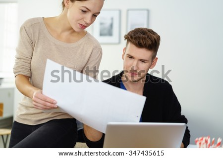 Couple looking at document searching information on internet in home interior - stock photo