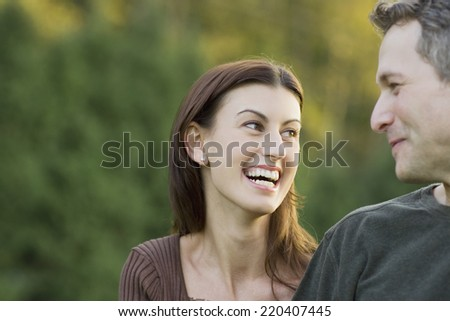 Couple looking at each other and laughing outdoors - stock photo