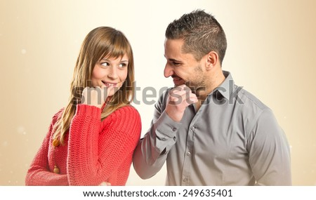 Couple looking at each other over ocher background