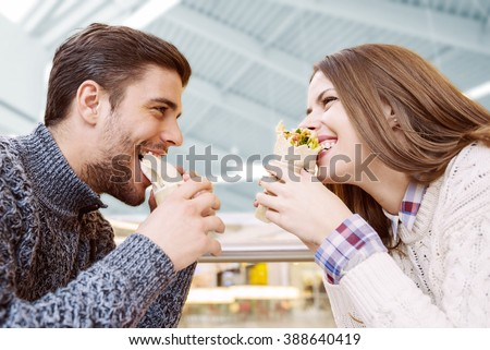 Couple looking at each other while eating fast food - stock photo