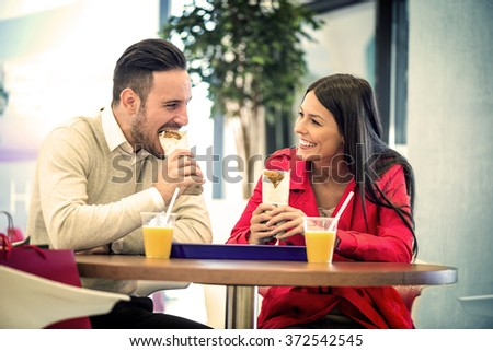 Couple looking at each other while eating fast food.Image taken inside a shopping mall. - stock photo