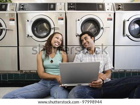 Couple looking at each other while sitting on the floor with laptop in laundromat