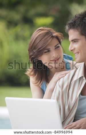 Couple looking at each other while using a laptop computer in home garden by swimming pool.