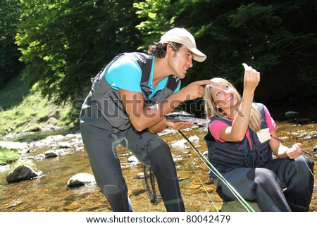 Couple looking at fishing flies in river - stock photo