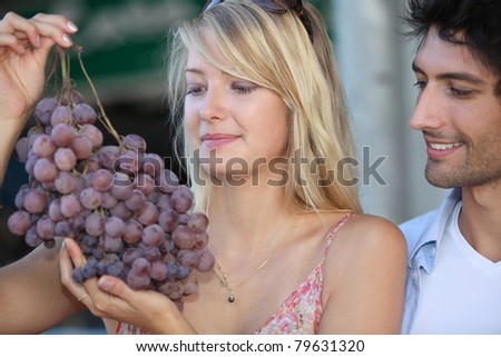 couple looking at huge bunch grapes - stock photo