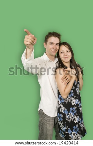 couple looking at imaginary point over green screen