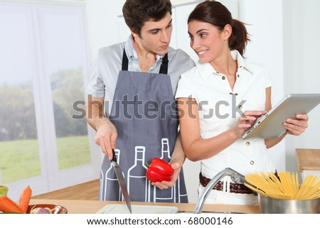Couple looking at italian recipe on electronic tab - stock photo