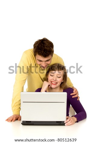 Couple looking at laptop together - stock photo