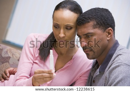 Couple looking at negative home pregnancy test - stock photo