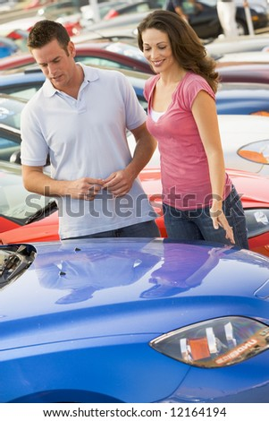 Couple looking at new cars on lot - stock photo