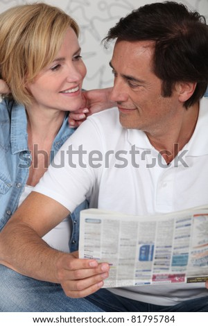 Couple looking at newspaper