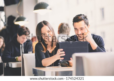 Couple looking at photos on tablet computer laughing - stock photo