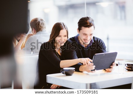 Couple looking at photos on tablet computer laughing in cafe - stock photo