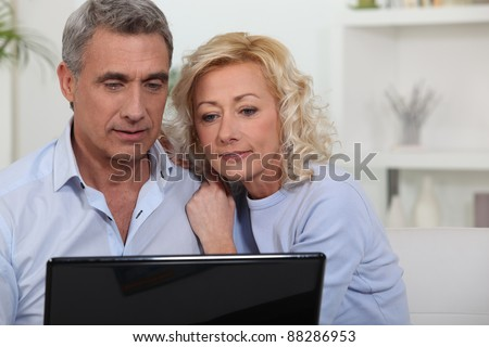 Couple looking at photos on their laptop - stock photo