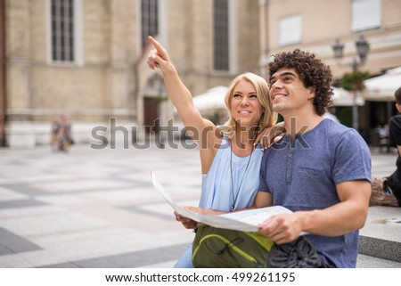 Couple looking at the map and sightseeing in the city.
