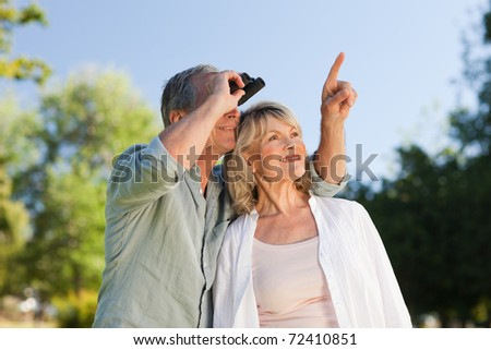 Couple looking at the sky with their binoculars - stock photo
