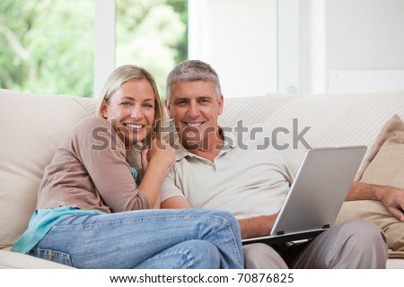 Couple looking at their laptop at home - stock photo