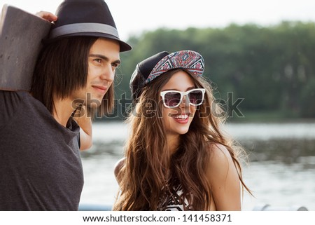 Couple looking away on the bank of a river. Young active people. Outdoors, lifestyle - stock photo