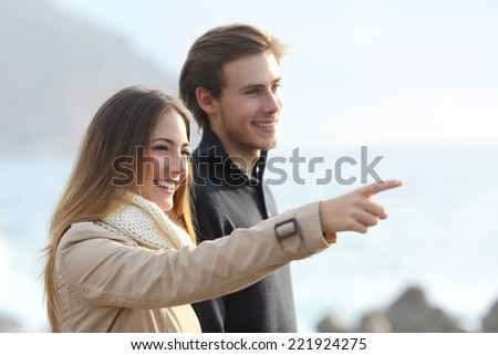 Couple looking forward on the beach and pointing at side with an unfocused background - stock photo