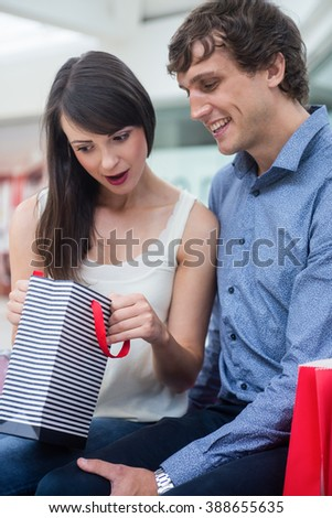 Couple looking in the shopping bag in mall - stock photo