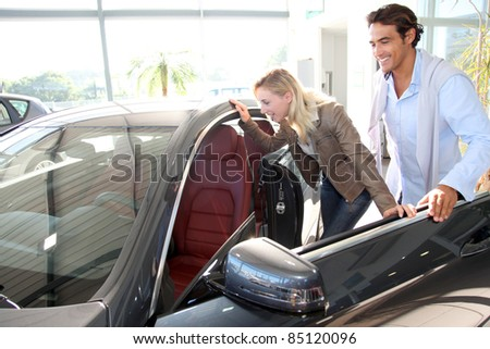 Couple looking inside new car - stock photo