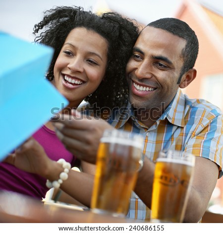 Couple Looking into Shopping Bag - stock photo