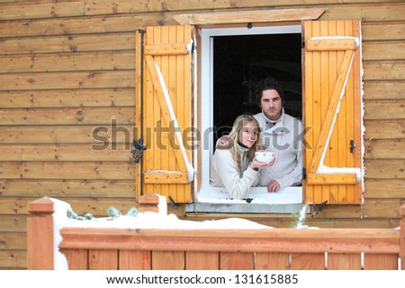 Couple looking out from chalet window - stock photo