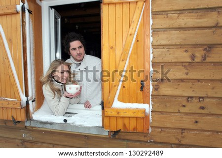 Couple looking out of their winter cabin - stock photo