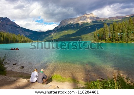 Couple looking out on beautiful Emerald Lake at dusk - stock photo