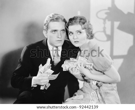 Couple looking scared with a fistful of money - stock photo