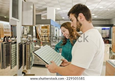 Couple looking tiled bathroom. They are in a warehouse that sells interior home and bathroom decoration - stock photo