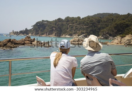 couple looking to shore from a boat - stock photo