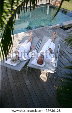 Couple lounging by a pool - stock photo