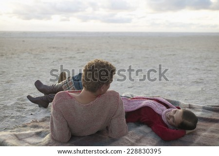 Couple lounging on a beach blanket - stock photo