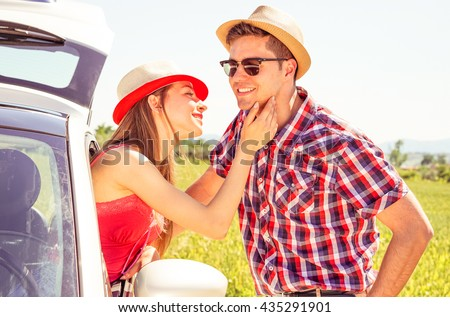Couple love moment at summertime road trip - Young woman caress boyfriend face from  car window on countryside background - Summer travel concept with models in romantic love and tenderness posing - stock photo