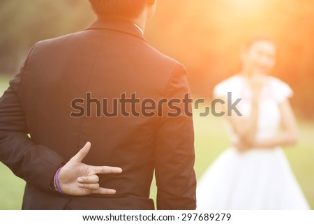 couple, love, proposal and holiday concept - close up of man hiding the hand of love sign behind from woman - stock photo