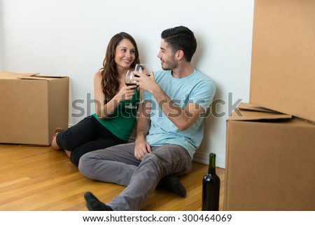 Couple lovers moving into new home cardboard boxes enjoying wine