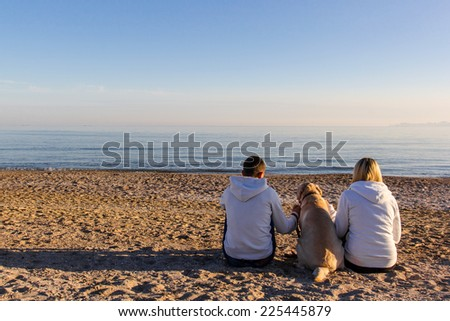 Couple Lovers sitting on the beach witn dog - stock photo