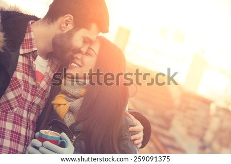 Couple loving each other outdoors on a coffee break. - stock photo