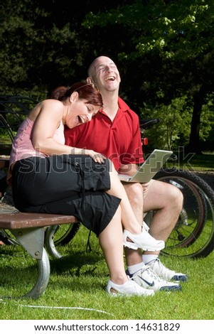 Couple lovingly sitting on a park bench laughing together. The man is holding a laptop computer and the woman is resting on his shoulder. Vertically framed shot. - stock photo