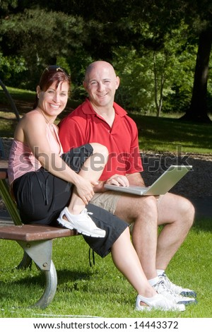 Couple lovingly sitting on a picnic table smiling and sitting at the park. The man is holding a laptop computer. Vertically framed shot. - stock photo