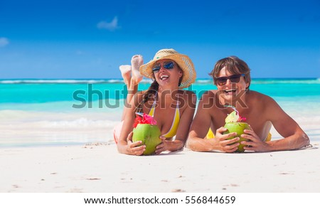 couple lyind and drinking a coconut cocktail on a tropical beach in Barbados