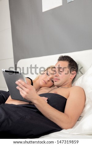 Couple lying close together cuddling in bed reading a tablet-pc with copyspace - stock photo