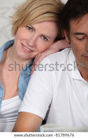 Couple lying dressed on their bed - stock photo
