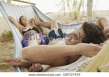 Couple lying in a hammock together at beach - stock photo