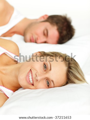 Couple lying in bed. Man sleeping and woman smiling at the camera - stock photo